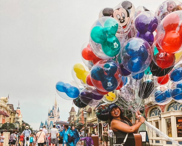 A woman wearing a baseball cap smiles and holds a bouquet of balloons in front of the Disney World castle.