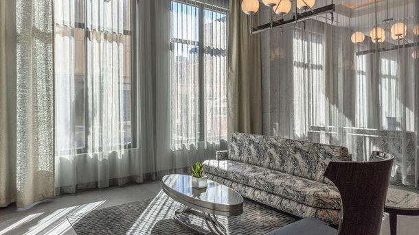 A chic and modern hotel lobby with a gray color scheme, including a marble print couch, reflective silver oblong coffee table, and sheer gray drapes.