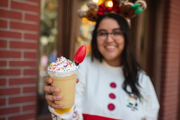 A woman holds out an eggnog milkshake with a light bulb in it, which is available at Mickey's Very Merry Christmas Party.