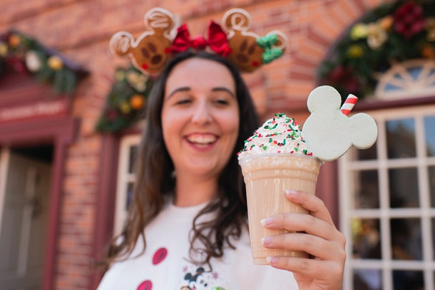 A woman holds a Christmas Cookie Shake in her hand at Mickey's Very Merry Christmas Party.