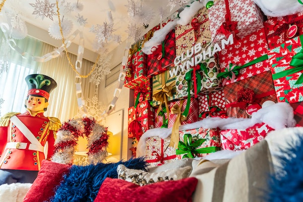 The 'Elf'-themed suite at Club Wyndham Midtown 45 has a wall of wrapped presents, a gigantic nutcracker, and colorful pillows on the couch.
