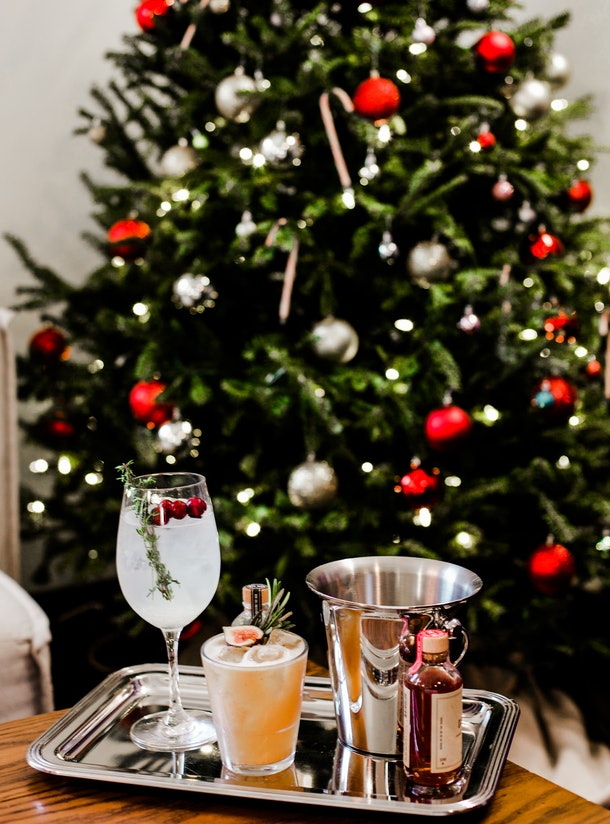 """A silver platter of seasonal cocktails sits on a wooden coffee table with a Christmas tree in the background as part of Refinery's """"Winter Spectacular Stay Package."""""""