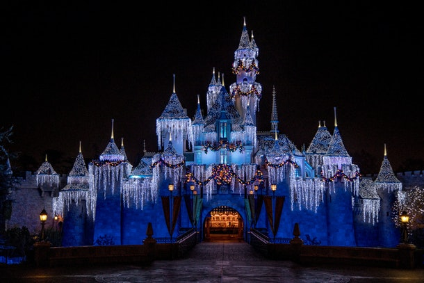Sleeping Beauty's Castle at Disneyland lights up for the holidays with Christmas decor and icicle lights.