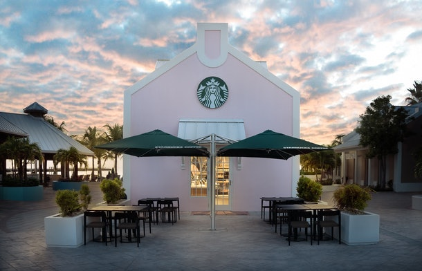 The exterior of Starbucks' Grand Turk store features a patio with green umbrellas and views of the beach.
