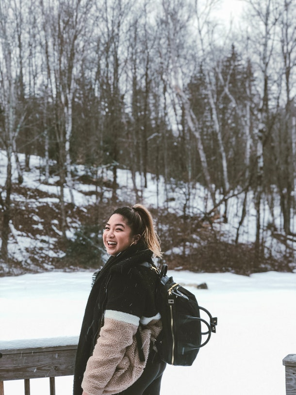 A smiling woman wearing a fuzzy coat and a backpack is surrounded by a field of snow and trees in the background.