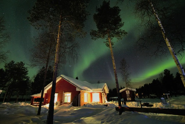 A cottage in the woods is covered in snow with the Northern Lights shining above.