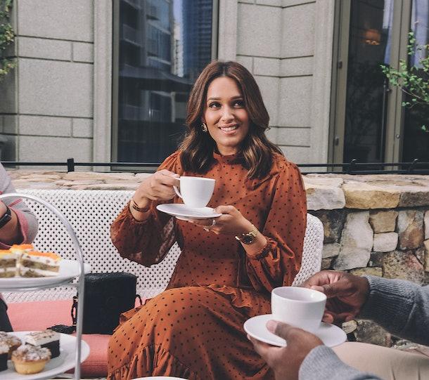 A stylish woman holds a cup of tea during Waldorf Astoria Atlanta Buckhead's holiday afternoon tea.