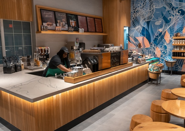 The interior of Starbucks' Grand Turk store has a tropical blue and pink wall and wooden accents.