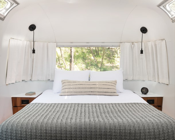 The interior of an AutoCamp airstream trailer features a cozy, neutral-colored bed with nightstands on either side.