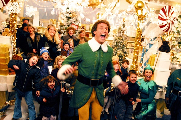 Buddy the Elf jumps and cheers while surrounded by kids in a holiday store in the Christmas movie, Elf.