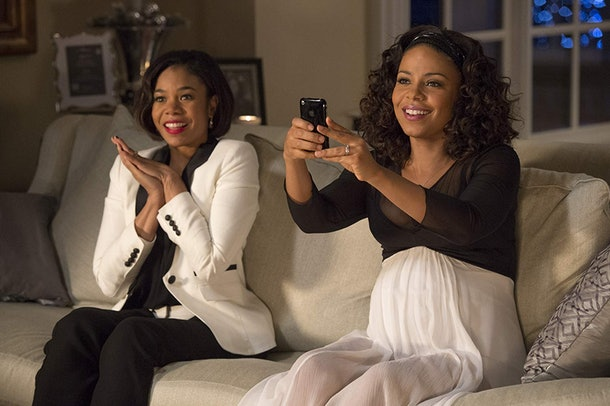 Two women sit on a couch, one holding her hands together and the other taking a picture, in The Best Man Holiday.