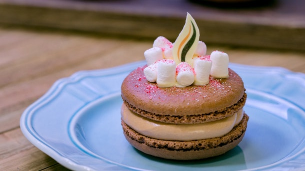 The hot cocoa marshmallow macaron has a white chocolate flame and marshmallows on top, and is offered at Disneyland's holiday celebration.