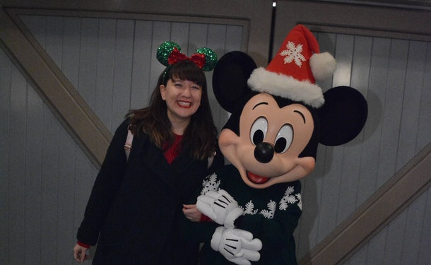 A smiling woman wearing festive red and green Minnie ears poses with Mickey Mouse at Disneyland during the holidays.