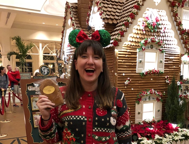 A smiling woman holds a gingerbread cookie and wears a Christmas sweater and festive Minnie ears at Disney.