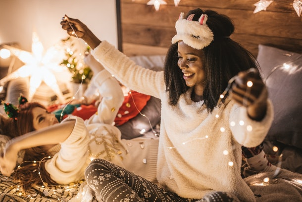 Black woman in bed holding Christmas lights
