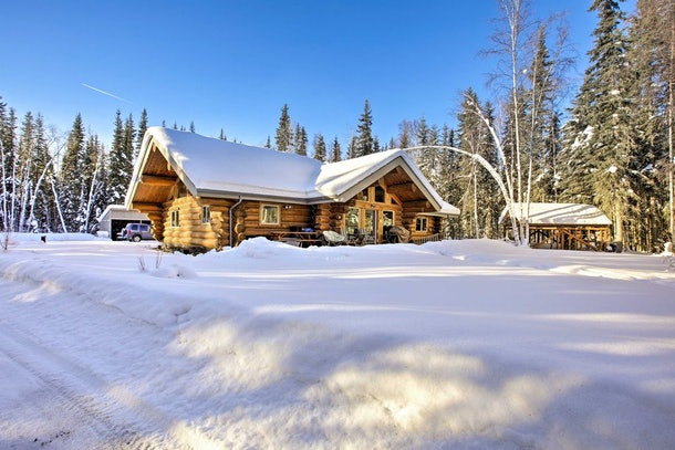 A cozy cabin in North Pole, Alaska is covered in snow and surrounded by tall evergreen trees.
