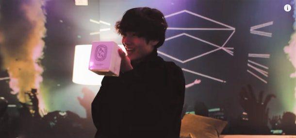 A screenshot from a video of BTS giving Halsey her Christmas gift.