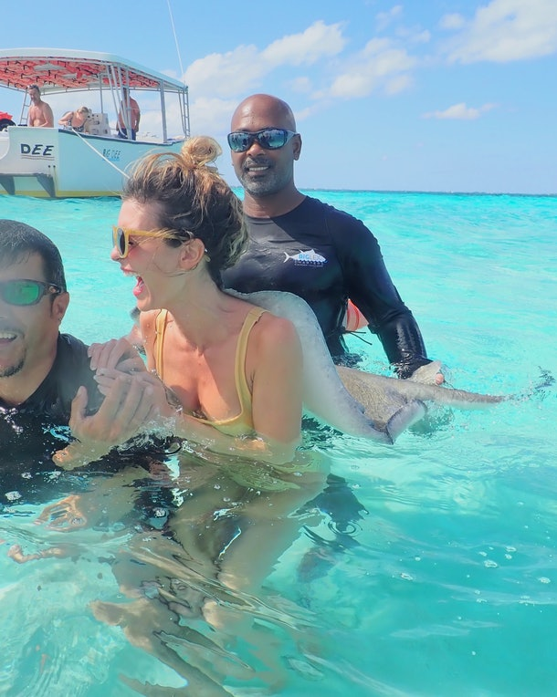 A girl in sunglasses and a bikini gets a stingray back massage in the water.