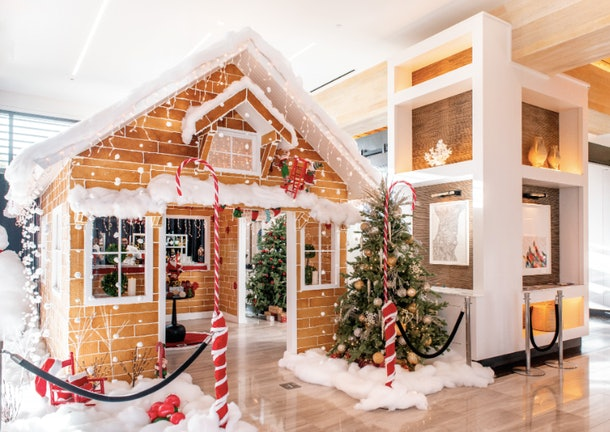 A life-size gingerbread cocktail bar is surrounded by fake snow, Christmas trees, and festive decor in the Kimpton Seafire Resort + Spa lobby.