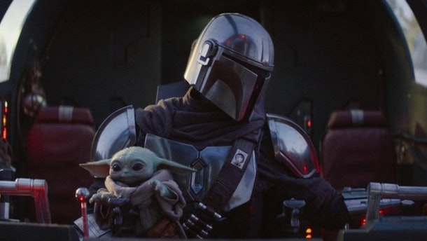 Baby Yoda sits in Mando's lap in 'The Mandalorian' while they ride in a spacecraft.