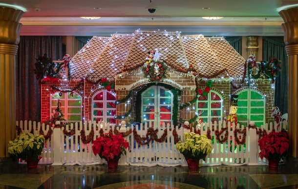 A giant gingerbread house with poinsettias surrounding it is on display on the Disney Cruise Line during the 2019 holiday season.