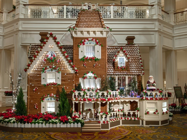 The giant gingerbread house decorated with poinsettia plans sits in the lobby of the Grand Floridian at Disney World.