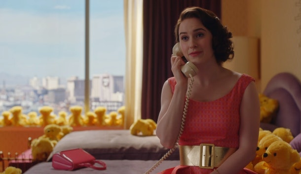 "A scene from 'The Marvelous Mrs. Maisel"" where Midge sits on a bed in a pink dress and is surrounded by yellow teddy bears while talking on the phone."
