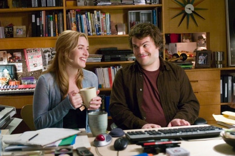 Jack Black and Kate Winslet smile sit in front of a piano with mugs of tea and laugh in a scene from 'The Holiday.'