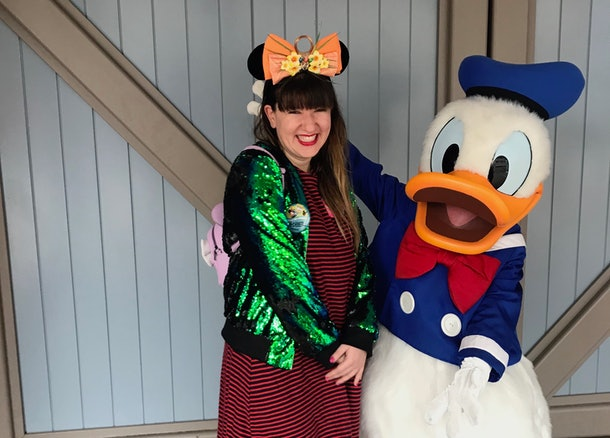 A woman stands next to Donald Duck at Disneyland on New Year's Eve.
