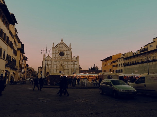 A Christmas market near the Basilica di Santa Croce in Florence is busy around sunset.