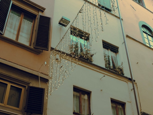 A set of twinkly lights hang over a street in Florence around Christmas.