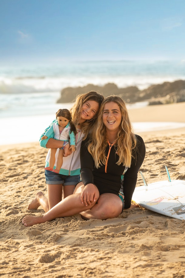 Olympic surfer Caroline Marks and sister sit on the beach with American Girl doll Joss Kendrick and a surfboard