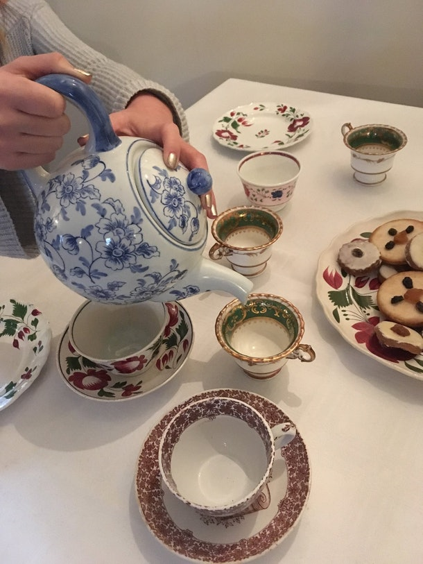 A woman pours tea as part of the museum tour and tea tasting experience through Airbnb.