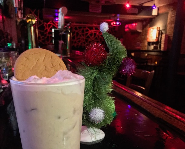 A 'Grinch'-inspired Gingerbread White Russian cocktail sits on the bar of the East Village Tavern with a Dr. Seuss Christmas tree behind it.