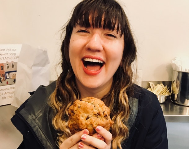 A happy woman holds a chocolate chip cookie and smiles.