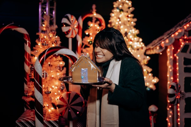 A woman smiles at her gingerbread house that she made at Santa's North Pole Village in LA.