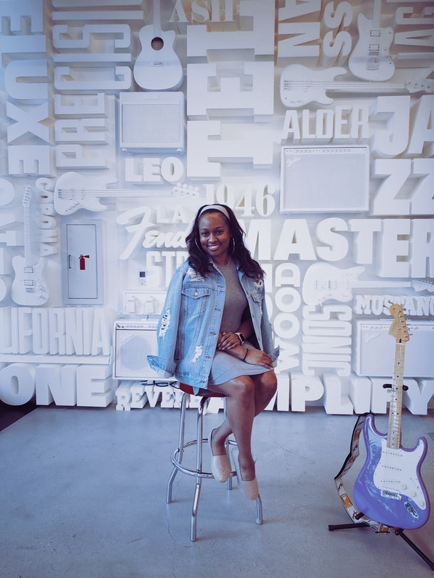 Moya Nkruma sits on a stool with a Fender guitar