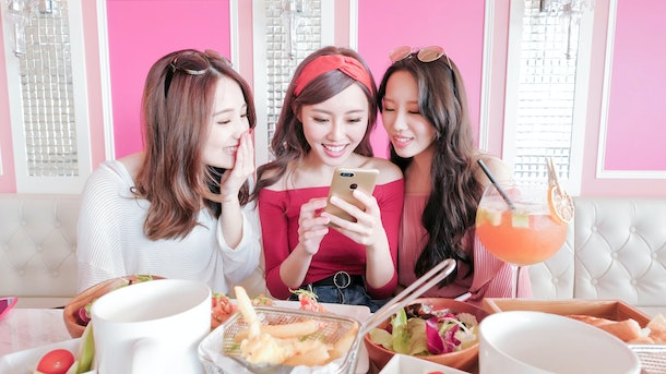 Three girls smile while looking at a cell phone at brunch.