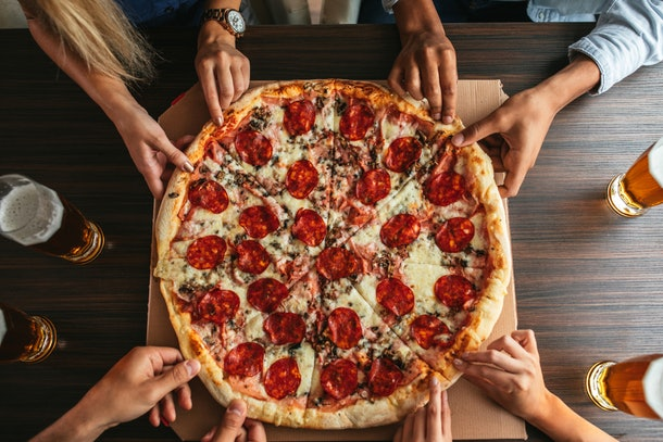 A group of people's hands digs into a pepperoni pizza.