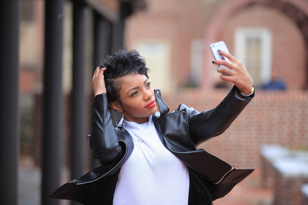 A happy, trendy woman in a leather jacket and turtleneck takes a selfie outside.
