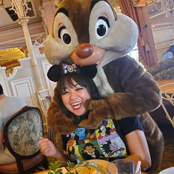 A woman wearing Mickey Mouse ears smiles with Dale at a Disneyland character breakfast.