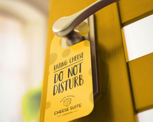A 'Do Not Disturb' sign hangs on the yellow door of the Cheese Suite by Café Rouge.
