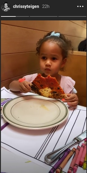 Chrissy Teigen and Luna eating pizza