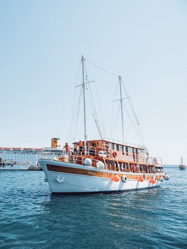 A boat with Contiki travelers on board sails through bright blue water in Europe during the summertime.