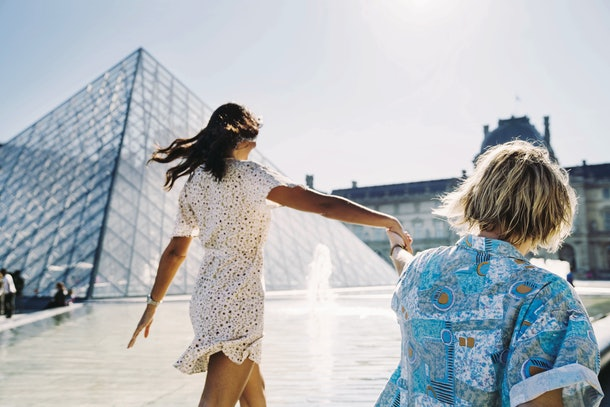 Two women walk near the Louvre in Paris on a sunny day.