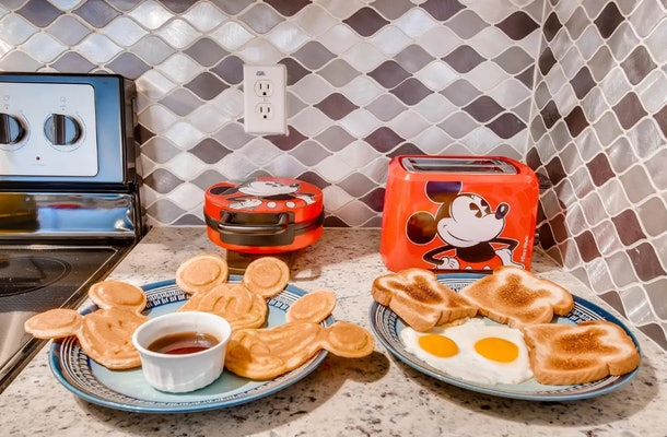This Mickey Mouse-themed Airbnb has Mickey kitchen appliances with plates of Mickey-shaped pancakes and toast.