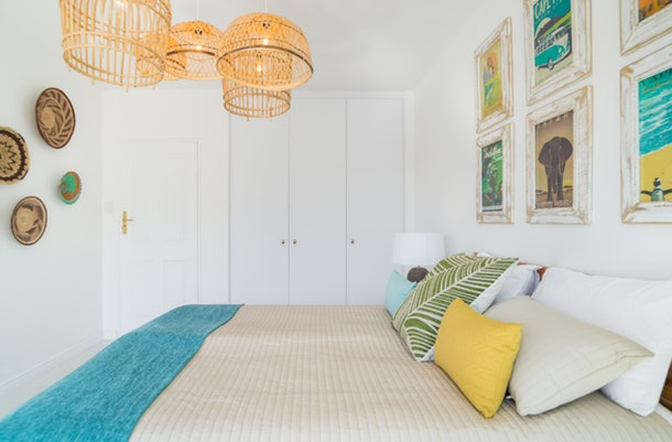 A cozy apartment in Cape Town, South Africa has white walls with framed prints, a bed with colorful pillows, and basket-style light fixtures.