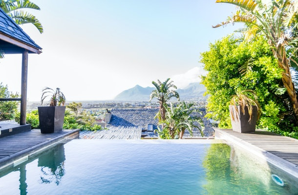 The terrace of a stunning villa in Cape Town, South Africa has an infinity pool and mountain views.