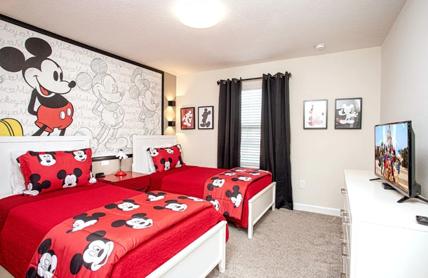 This Mickey Mouse-themed Airbnb has Mickey bed sheets in the bedroom.