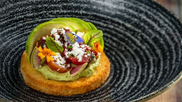 The avocado toast served at Epcot's International Festival of the Arts sits on a plate.
